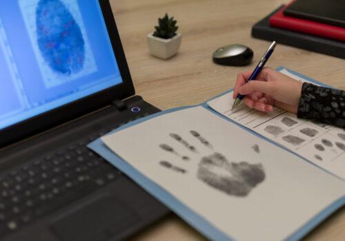 The forensic expert studies the fingerprints taken of a suspect. Detective expert writes data into the fingerprint table